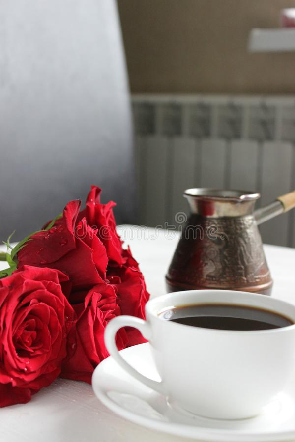 A Cup of coffee and a bouquet of red roses on the table close-up. royalty free stock image