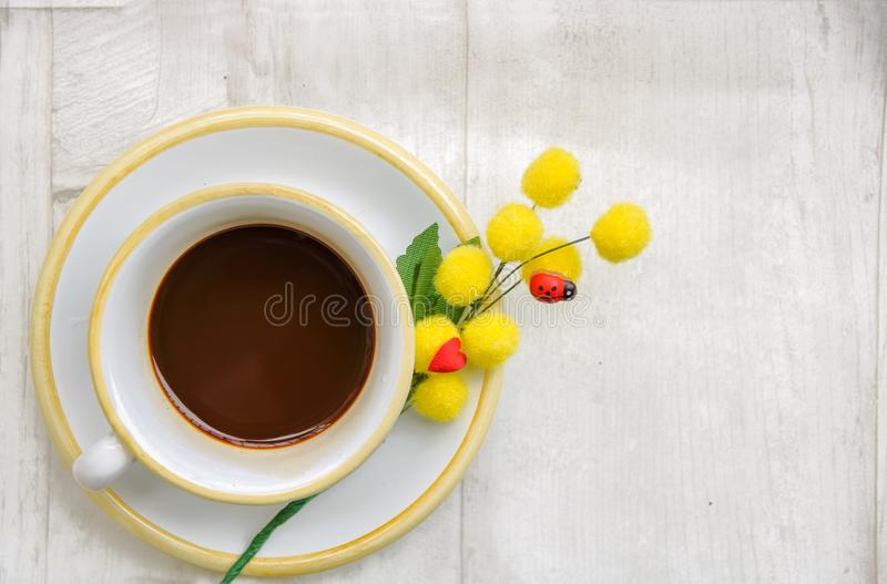 A coffee om springtime. Cup of coffee with a branch of mimosa and a little ladybug, as a symbol of springtime and international women`s day royalty free stock photos