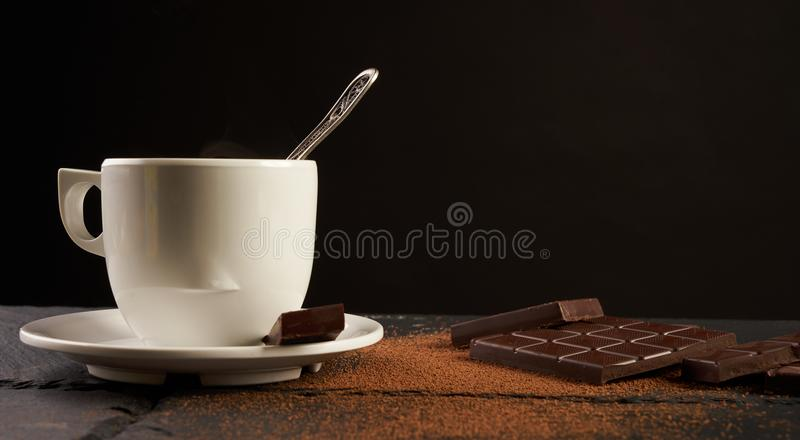 Cup of coffee with broken chocolate pieces. And cocoa powder on black stone background with copy space royalty free stock image