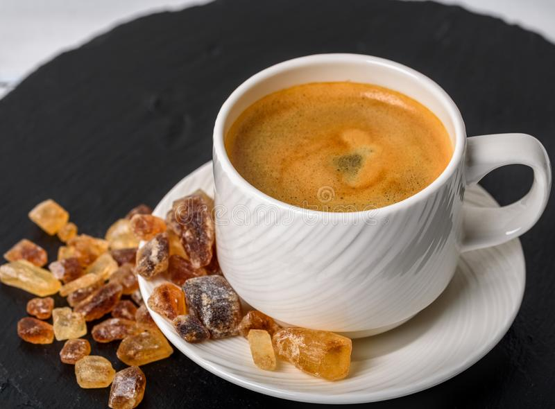 Cup of coffee and brown sugar cubes near it on the black stone b stock photography
