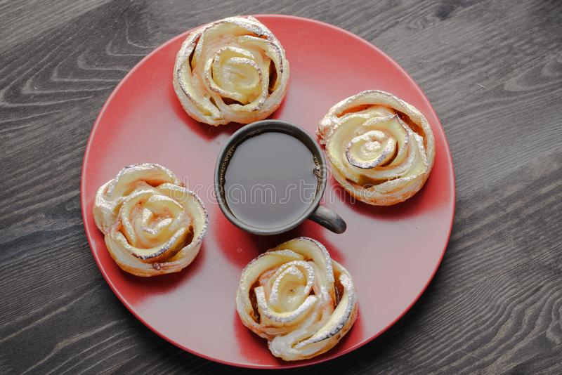 Biscuits with jam. Cup of coffee and a bun in the form of a rose,homemade buns with jam,homemade baking,puff pastries with a cup of coffee royalty free stock photos