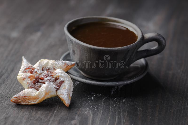 Biscuits with jam. Cup of coffee and a bun in the form of a rose,homemade buns with jam,homemade baking,puff pastries with a cup of coffee royalty free stock images