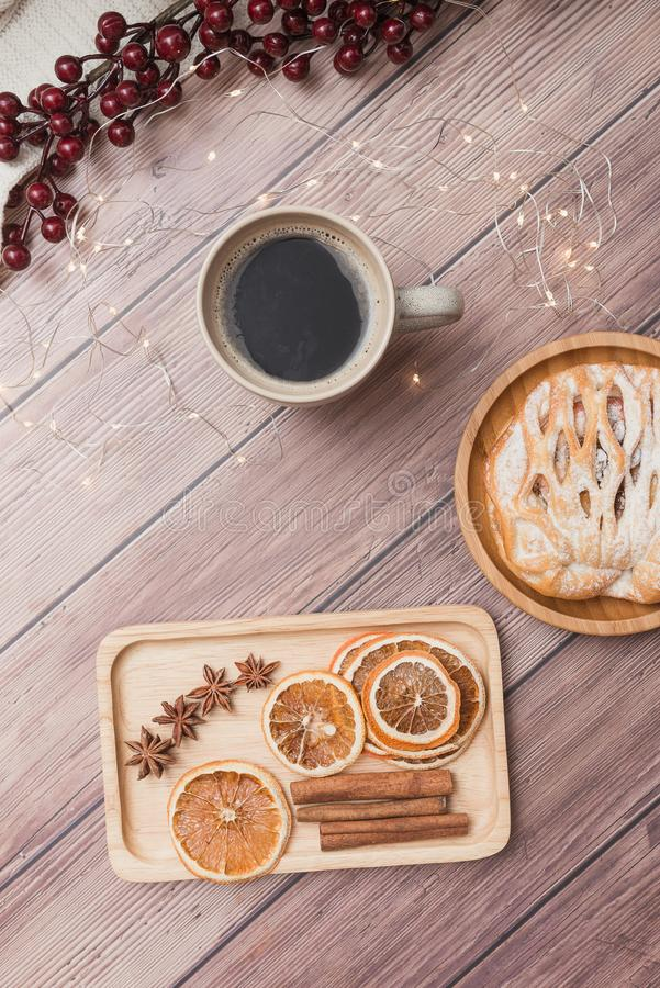 Cup of coffee with bun on wooden table, dried orange and cinamon, berries and Christmas lights, top view. Winter drinks flat lay stock photography