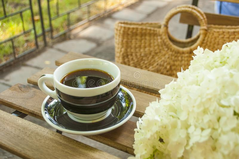 A cup of coffee in a cafe. A cup of black coffee on a wooden table and a straw bag with hydragea flowers on the background royalty free stock images