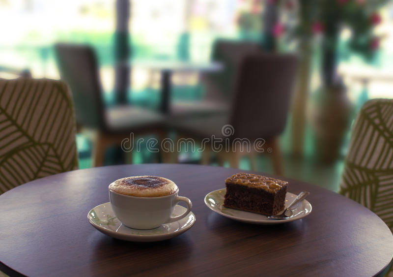 Cup of coffee and a cake on the table in cafe royalty free stock images