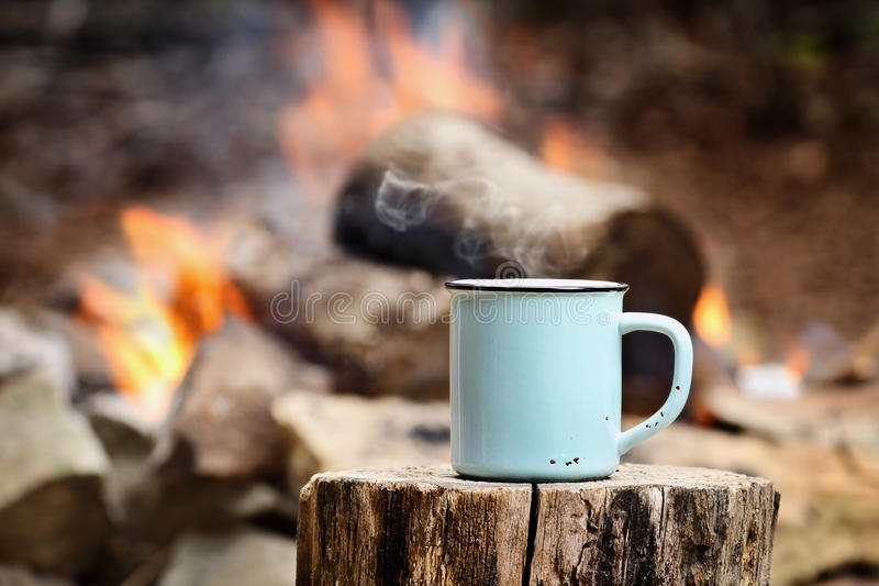 Cup of Coffee by a Campfire. Blue enamel cup of hot steaming coffee sitting on an old log by an outdoor campfire. Extreme shallow depth of field with selective stock image