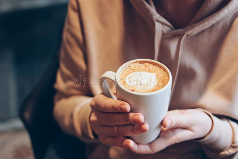 Cup of coffee cappuccino with foam heart in female hands at cafe, close up stock photos