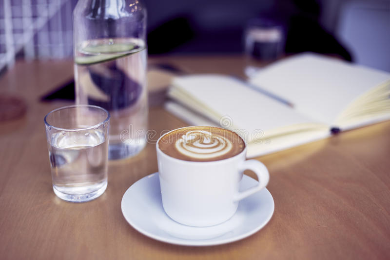 Cup of coffee cappuccino, glass of pure water, bottle on wooden table, bright interior daylight royalty free stock photography