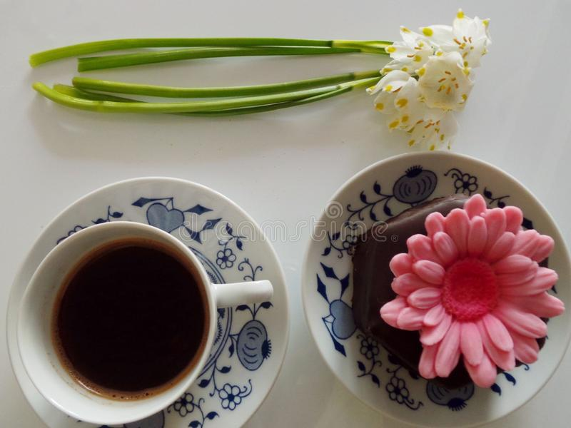 Cup of coffee, chocholate muffin with pink flower, snowdrops, from above stock image