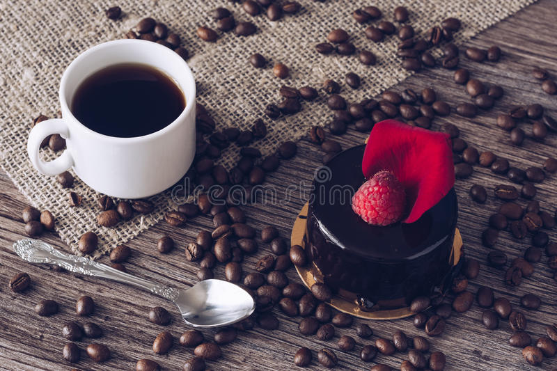 A cup of coffee with a chocolate cake with raspberries. A delicious dessert royalty free stock photography