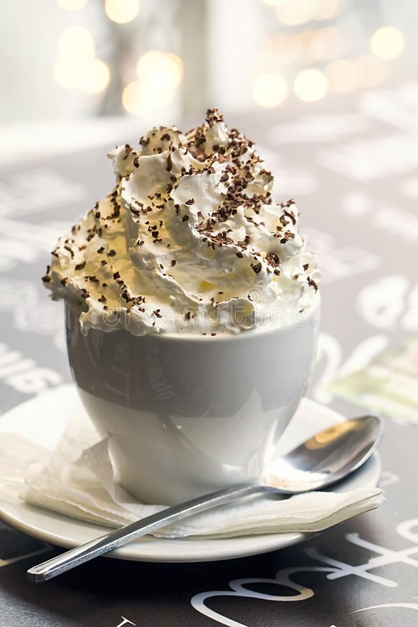 Cup of coffee with chocolate and whipped cream on the table in the cafe royalty free stock photo