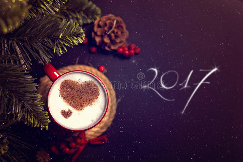 Cup of coffee on Christmas card. Cup of coffee with cinnamon hearts , rowan and cone on dark background and 2017 written royalty free stock images