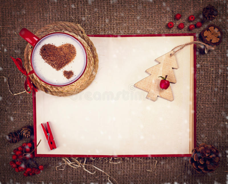 Cup of coffee on Christmas card. Cup of coffee with cinnamon hearts , wooden pine , pin, rowan and red book with space for your text on Christmas card royalty free stock photo