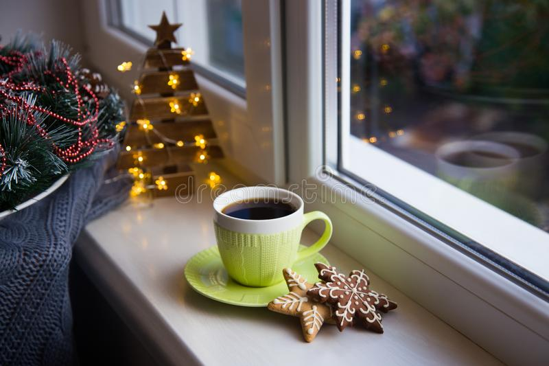 Cup of coffee and Christmas cookie near window in daylight with festive decoration and warm lights on background. Cup of coffee and Christmas cookie in form of stock image