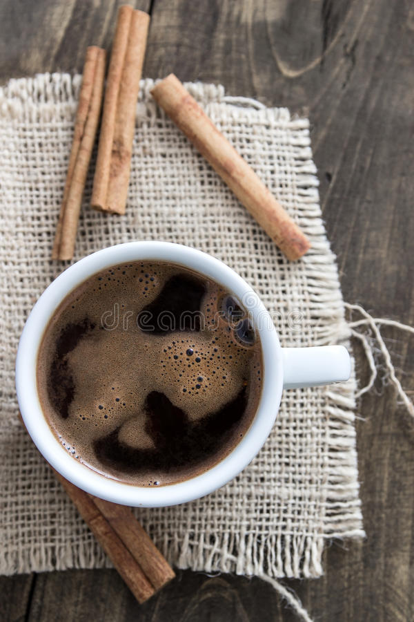 Cup of coffee with cinnamon sticks stock photo