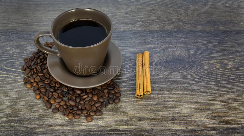 Cup of coffee and cinnamon on wooden table, delicious dessert royalty free stock photo