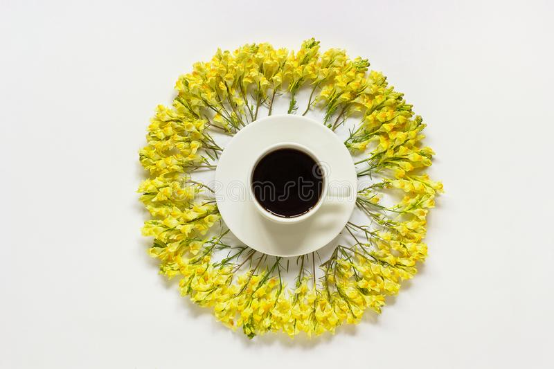 Cup of coffee and circular frame yellow wild flowers Linaria on gray background Flat lay Top view Concept Good morning or Hello. Spring Template for postcard royalty free stock images
