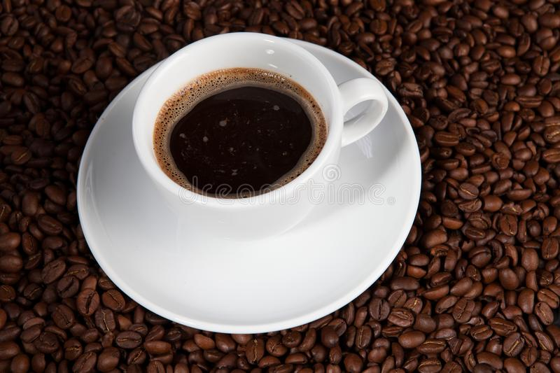 White cup of coffee at coffee beans backgrounds royalty free stock photos