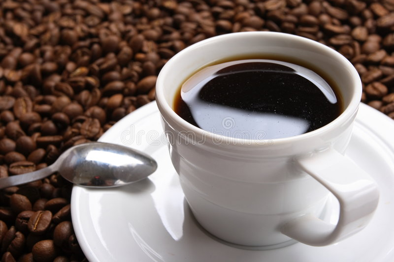Cup coffee And coffee grain. Cup with coffee, costing on coffee grain royalty free stock photography