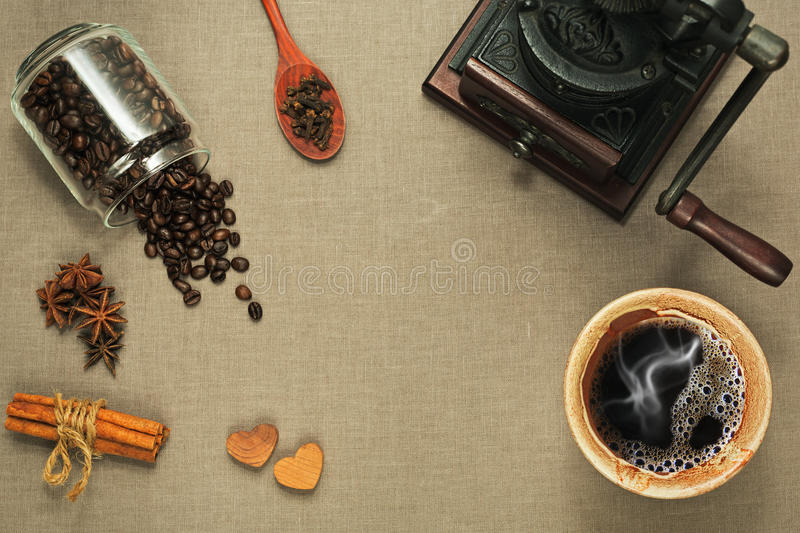 Cup of coffee, coffee mill and different spices on rude textile royalty free stock images