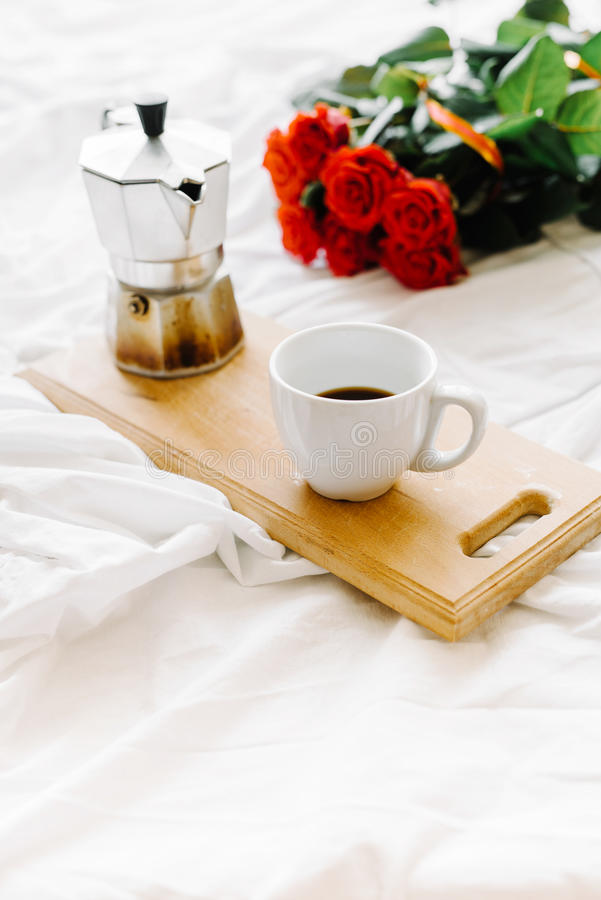 A cup of coffee, coffee on the wooden Boards, a bouquet of red roses on a white background royalty free stock photos