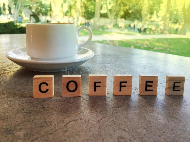 Cup of coffee and coffee word. On table royalty free stock photography