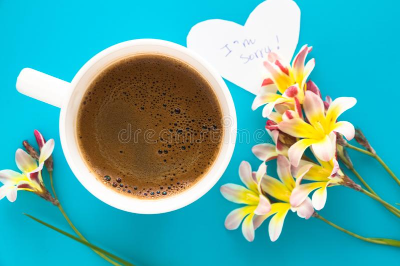 A cup of coffee with colorful flowers and apology note. A cup of coffee with colorful flowers and apology note, on blue surface royalty free stock photo