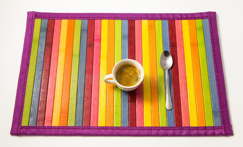 Cup of coffee in a colorful wood background. Aerial view of a cup of coffee in a colorful wood background royalty free stock photo