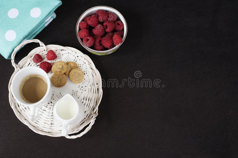 Cup of coffee, cookies a jug of milk on a straw tray. A bowl with raspberries. Black background. Top view royalty free stock photo