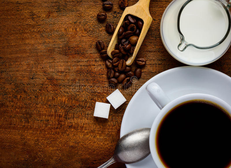 Cup Coffee and Copy-Space. Top view of wooden table-top with Cup of Coffeee, Coffee-Beans, sugar and milk with copy-space royalty free stock photos