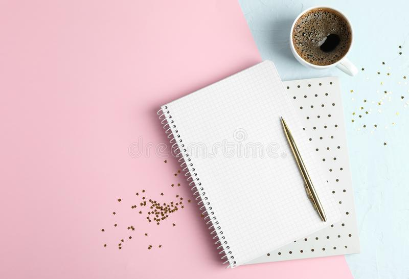Cup of coffee with copybooks, glitter stars and pen on color background royalty free stock images
