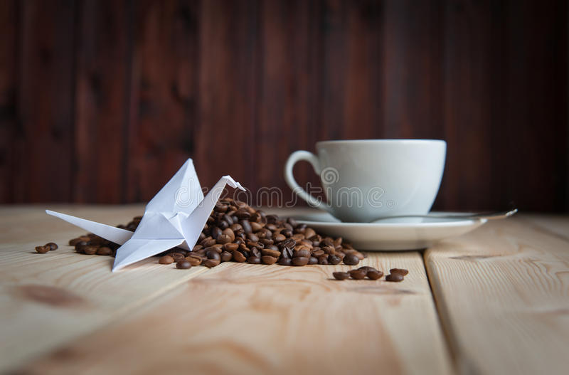 Cup of coffee with crane. Origami on the coffee beans royalty free stock photo