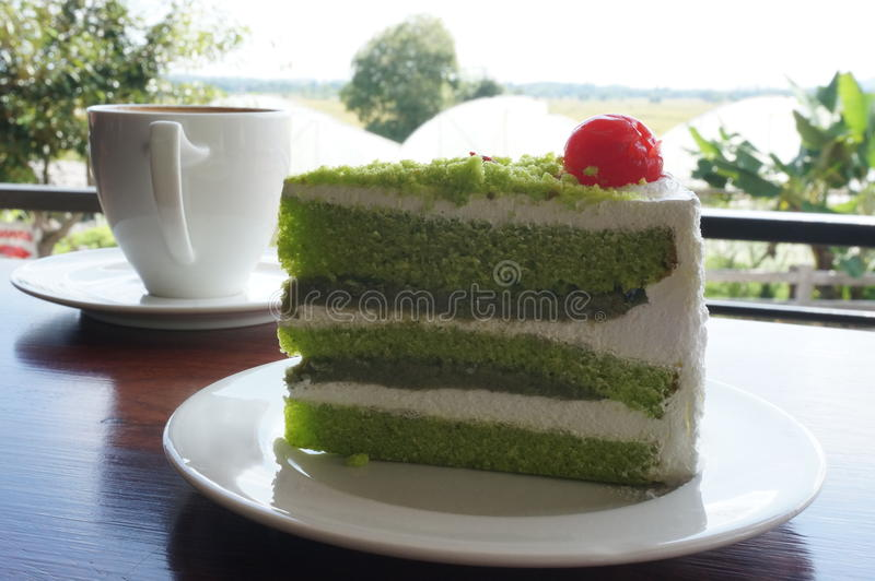 A cup of coffee and cream pandan cake on wood table royalty free stock photo