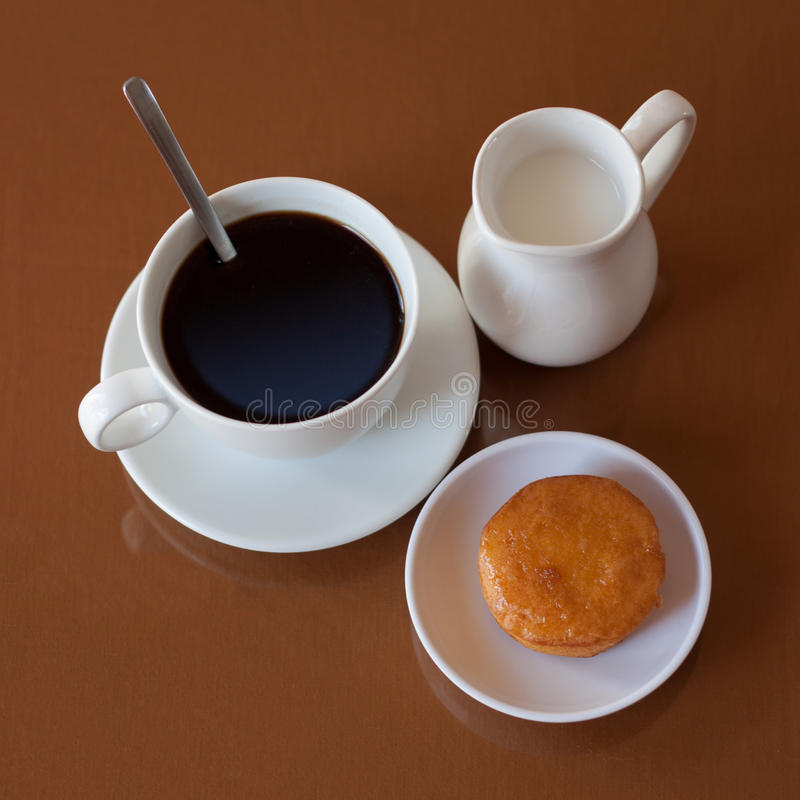 Cup of coffee, creamer jug and muffin on reflective table. Top view stock image