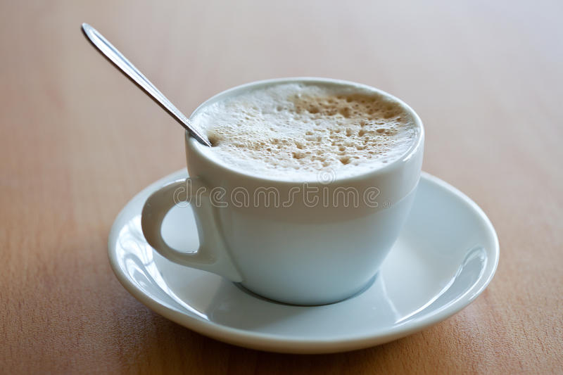 Cup of coffee with crema. White cup of coffee with crema on the wood table royalty free stock image