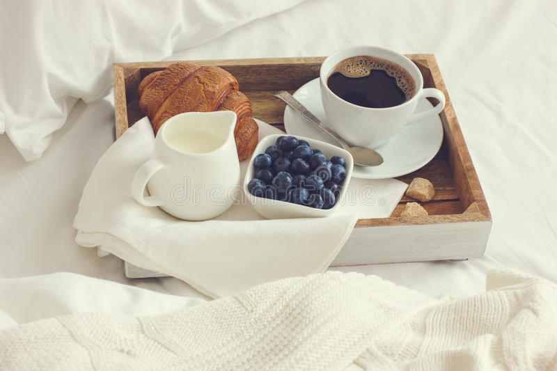 Cup of coffee, croissant and fresh blueberry on wooden tray, bre royalty free stock photography