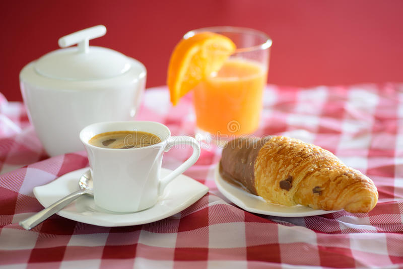 Cup of coffee, croissant, orange juice and a sugar bowl stock images