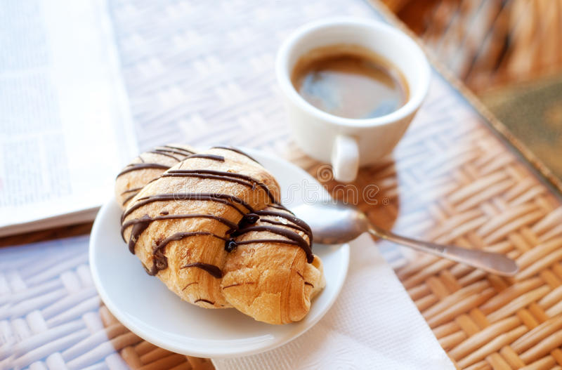Cup of coffee and a croissant on the table royalty free stock images