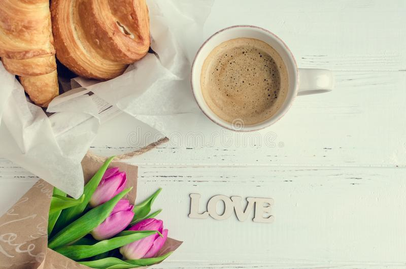 Cup of coffee with croissants, bouquet of pink tulips and wooden word LOVE. On white shabby chic background. Romantic Valentines morning concept. Valentine`s stock image