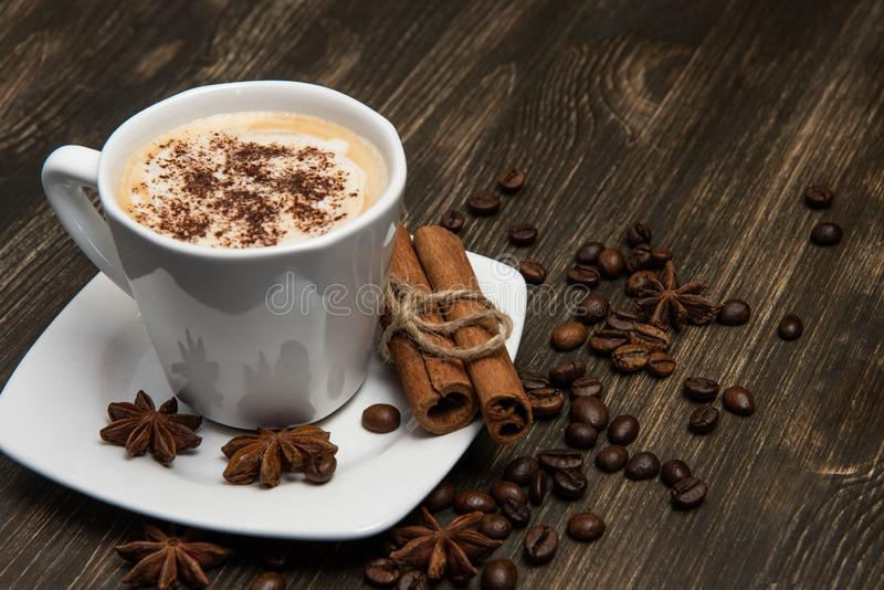 Cup of coffee on dark background. With cinnamon sticks, coffee beans and star anise stock image