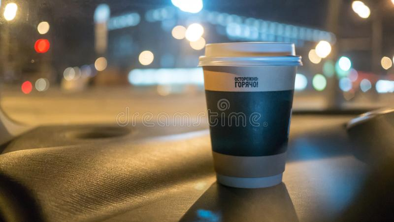 A cup of coffee is on the dashboard of the car royalty free stock images