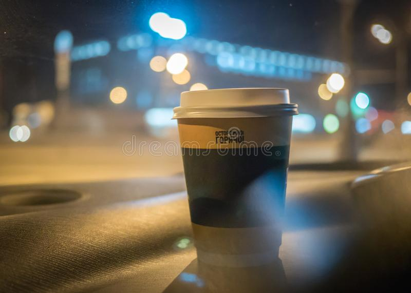 A cup of coffee is on the dashboard of the car royalty free stock photo