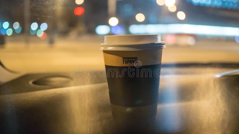A cup of coffee is on the dashboard of the car royalty free stock photography