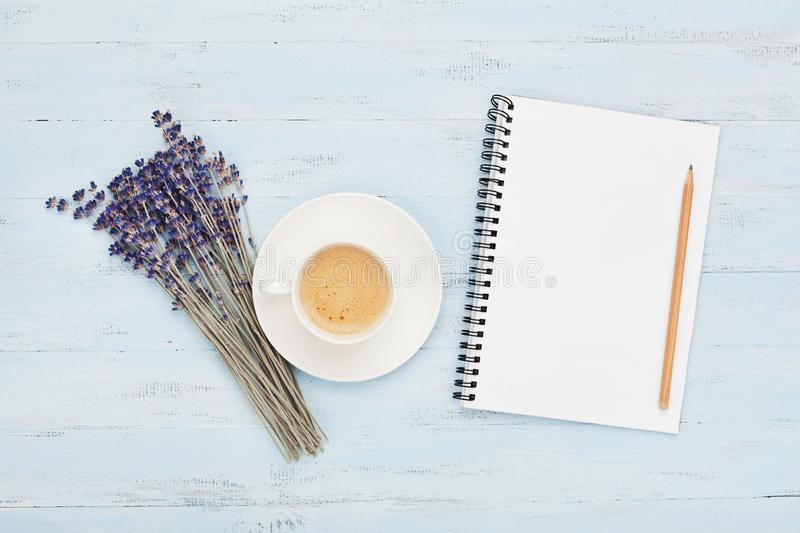 Cup of coffee, empty notebook and lavender flower on blue table top view. Woman working desk. Cozy breakfast. Flat lay style. Cup of coffee, empty notebook and royalty free stock photos