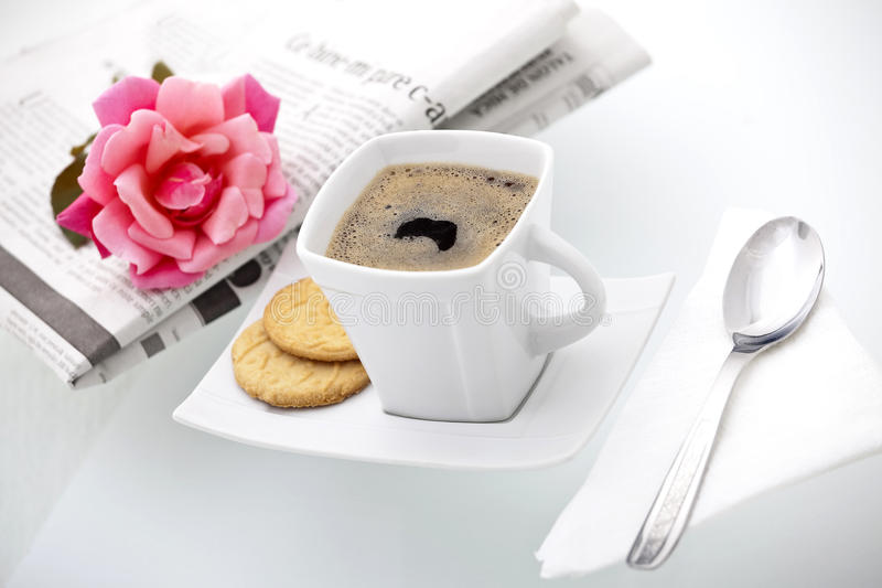 A cup of coffee enclose by a newspaper and a rose stock photos