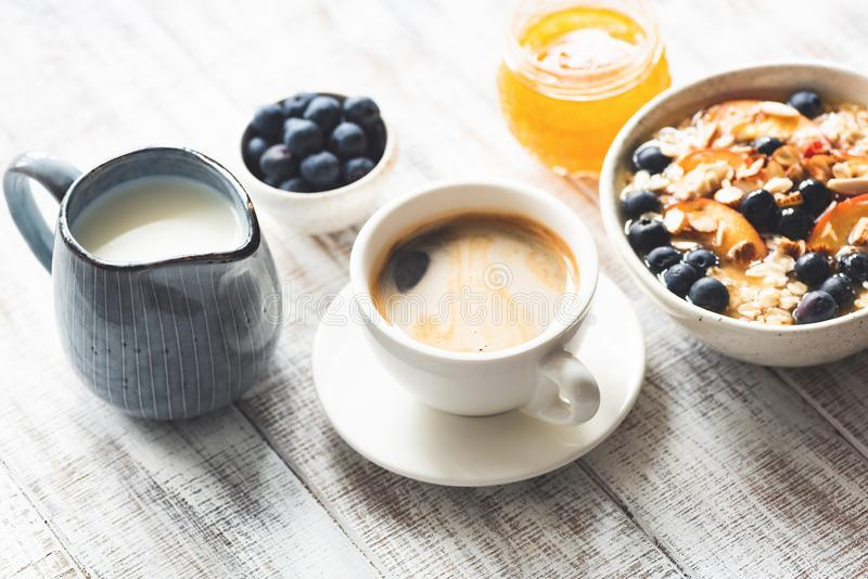 Cup of coffee espresso and breakfast food. Oatmeal porridge with fruits, berries, honey on rustic white wooden table background royalty free stock photo