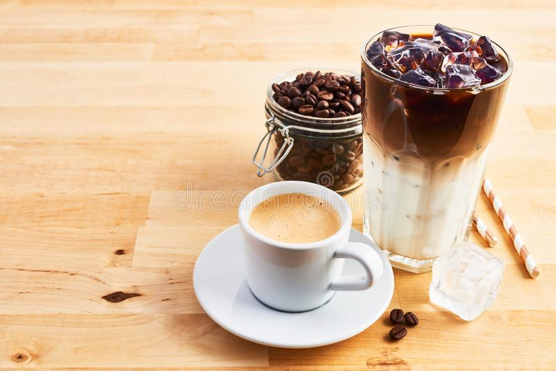 Cup of coffee or espresso, iced coffee and latte macchiato. In tall glass with straws on wooden table. Various types of coffee. Copy space for text stock photography