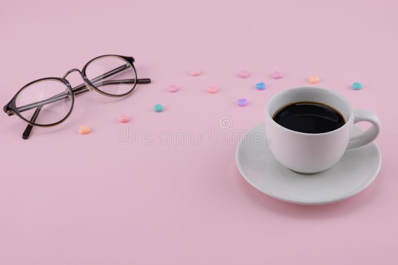 A cup of coffee and eyeglasses decorate with pastel heart pattern royalty free stock photo