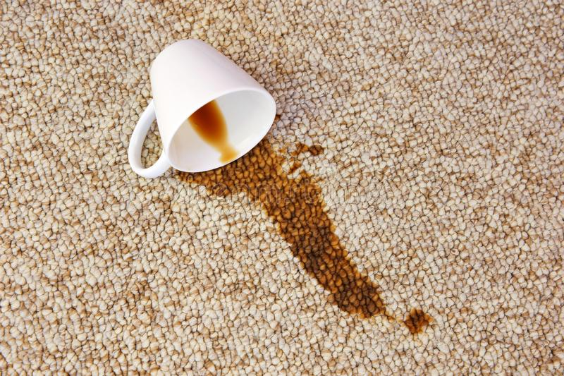 Cup of coffee fell on carpet. Stain is on floor.  royalty free stock photos