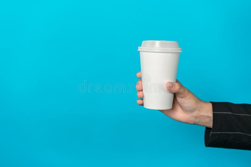 Cup of coffee in female hand with light blue background. Drink in a white paper cup stock image